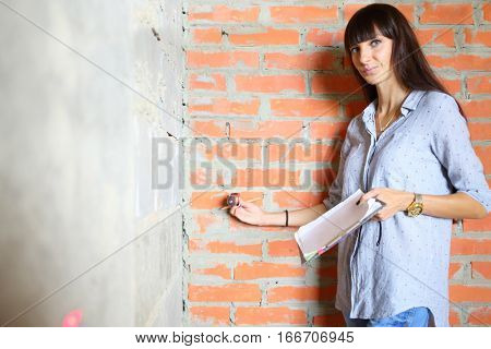 Woman with long hair making marks on the wall using a laser level on a construction site