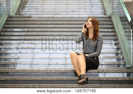 A young woman sitting on the marble staircase and talking on mobile