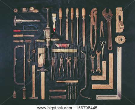 Old and rusty tools on a black background. Flat lay and top view