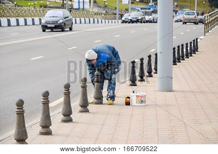 BELARUS MINSK - APRIL 08/2015: Worker cleans and paints the columns along the way.