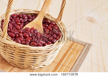 Raw adzuki red beans in woven basket on wooden background. Copy space