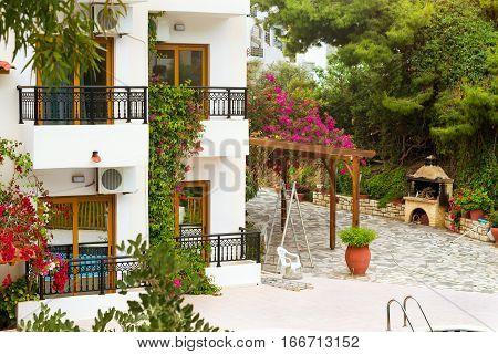 Modern and classic resort Greek architecture new white building in constructivist style stands on shore of Cretan sea. Resort village Bali Rethymno Crete Greece