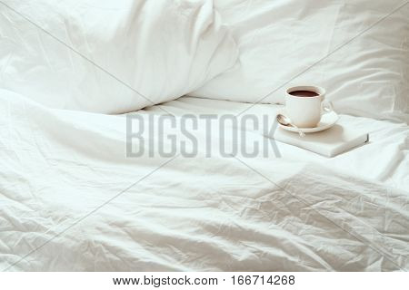 Open white, rumpled bedding with coffee and book. Room for copy.