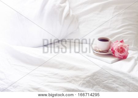 Open white, rumpled bedding with coffee, book and flower. Room for copy.
