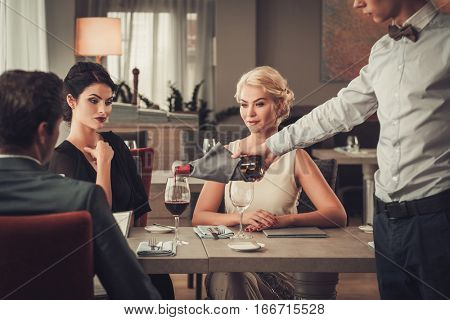 Waiter pouring red wine to group of elegant people in restaurant