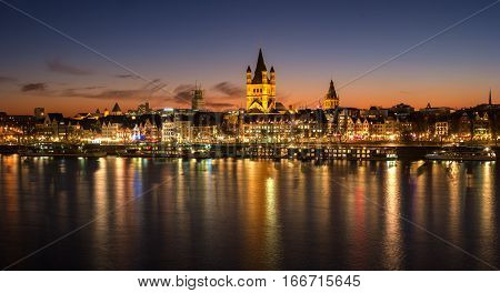 Cologne, Germany - January 22, 2017: View of the historic center of Cologne at dusk - Church of Gross St. Martin and the Town Hall. On the Rhine River are walking ships.