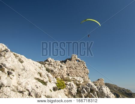 Green paraglider over the deep blue sky