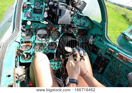 Girl sits in cabin of old jet fighter MiG-21 holding the control stick view at the controls