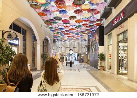 DUBAI UAE - DEC 2 2016: Shoppers taking pictures of colorful umbrellas in the Dubai Mall. United Arab Emirates Middle East