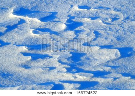 Freshly fallen snow in drifts and patters shadows winter