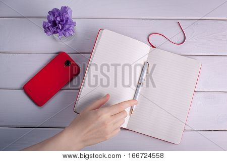 Woman's hand reaches for a ball-point pen. The thoughts in a notebook.