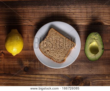 Table with lemon, avocado and bread