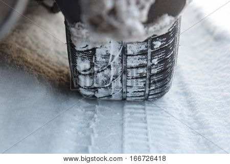 A closeup picture of a tire leaving tracks in the snow