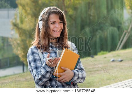 university student. pretty varsity girl with books headphones cellphone and a beautiful smile listening to music outdoors in the green campus park.