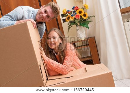 couple moving boxes for relocating to new house. happy young couple smiling renting a new house sitting next to cardboard boxes while packing with positive expression
