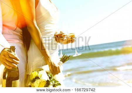 Midsection of newlywed couple with champagne bottle and flutes on beach