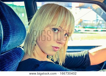 Blonde girl sits behind the wheel of a car. Vintage processing style,