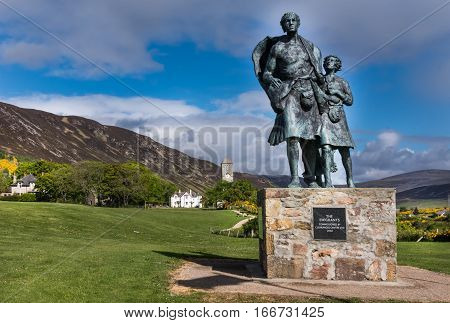 Helmsdale Scotland - June 4 2012: The Emigrant Statue at the south entrance of the town. The male side. Set on green hill with town in background.Blue sky with gray clouds bronze with green spots.