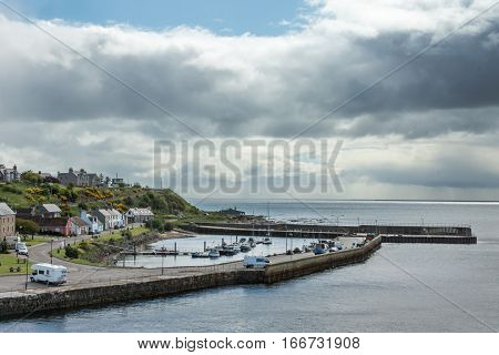 Helmsdale Scotland - June 4 2012: Wide shot on the harbor with part of the town. View on North Sea under heavy cloudy sky. Boats and trucks in harbor.