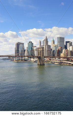 Lower Manhattan with Brooklyn Bridge at sunny day.