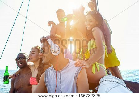 Happy friends enjoying boat party with music and beer at sunset - Happy friends enjoying summer vacation with dj set - Holidays and fun concept - Focus on man with headphones - Warm filter