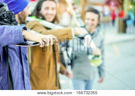 Happy friends walking to ski lift with snow sport equipment - Young people having fun in winter resort vacation - Happiness and friendship concept - Focus on left man hand finger - Warm filter