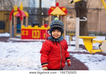 Small boy playing outside. Portrait of 2 year old toddler with blond hair and blue eyes.