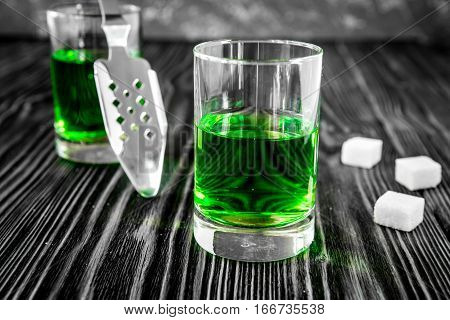 absinthe with sugar cubes and spoon on wooden background close up.