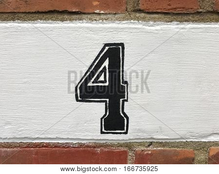 Number four hand painted black house address sign on painted white brick wall textured background