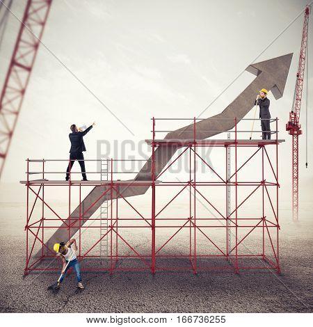 Teamwork builds an arrow uphill under construction. Build a business success. Mixed media