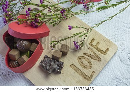 Box of chocolate candy and flower on a cutting board marked with the word Love for Valentine's Day