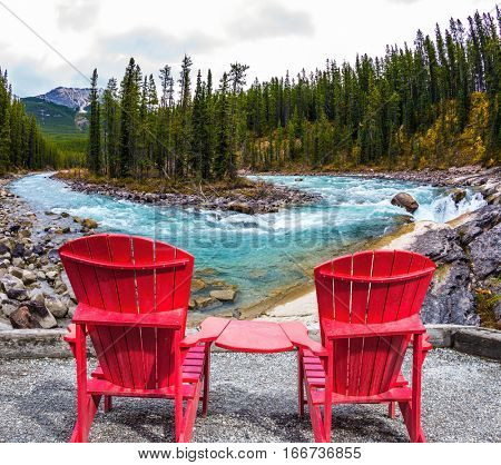 Two red deckchairs stand on the shore of the waterfall. Canada. Small island in the middle of the river. The concept of extreme and ecological tourism