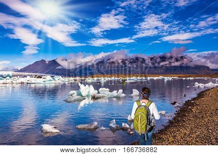 The concept of extreme northern tourism. Ice floes are reflected in the water. The woman - tourist with green backpack watching the sunrise in Ice Lagoon
