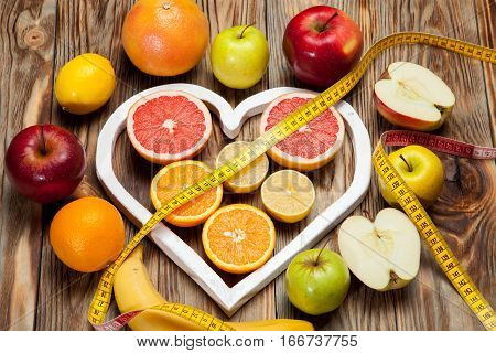Fruit Diet, centimeter and a heart on a wooden background