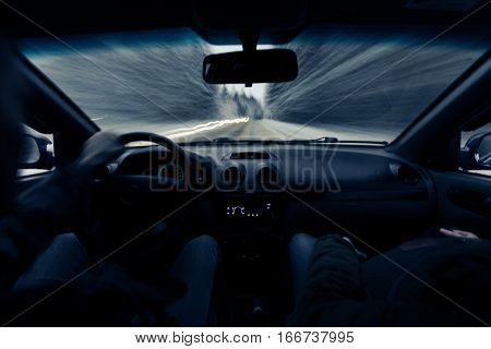 driving a car on winter road. Two people riding in a car inside view