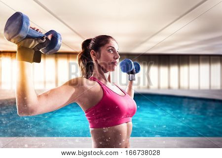 Muscular woman is training with weights dumbbells at the gym with swimming pool