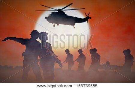 Military helicopter rescue mission during sunset silhouette