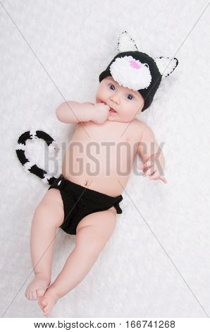 Beautiful baby in a funny costume with cat ears and a tail.