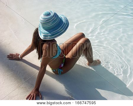 Woman sitting on swimming pool beach taking sun wearing summer cap.