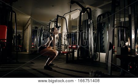 The view from the side. Woman squatting with barbell in a dark room. Girl holding a barbell on the shoulders.