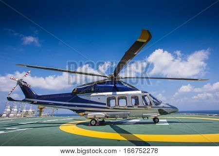 Helicopter or chopper land at oil and gas platform accomodation area for recieve and sent passenger from onshore hangar to offshore platform