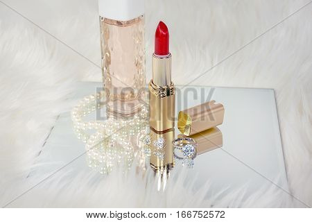 red lipstick  in gold tube with pearls and diamond jewelry on mirror in white fur
