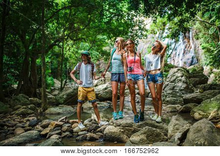 european tourists hiking in thailand standing on rocks by stream