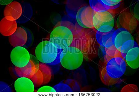 bright colorful circles of red green blue bokeh effect abstract dark black background