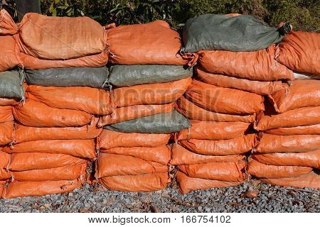 orange and grey sandbags stacked, ready for use