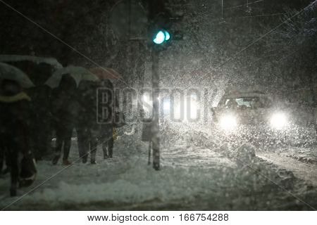 People with umbrellas walking in the street next to aggravated traffic due to strong snowfall.