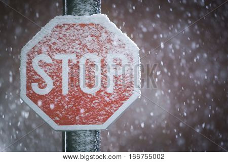 A close up of a traffic stop sign covered in snow during snowfall.
