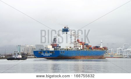Oakland CA - January 20 2017: Tugboat SANDRA HUGH at the stern of Cargo ship ANL BINDAREE assisting the vessel to maneuver out of the Port of Oakland