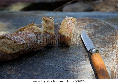 Sliced baguette with knife on rustic stone background. French picnic.