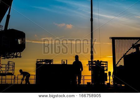 Silhouette of oil and gas wellhead platform and well service worker while working to perforation production tubing at gas reservoir.
